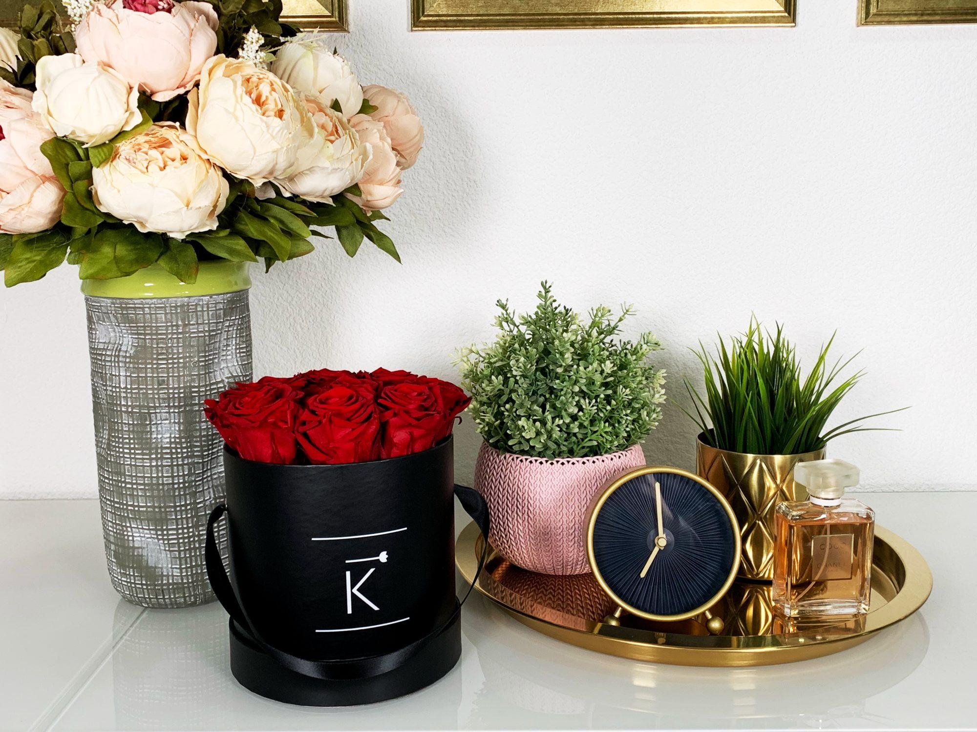 Schwarze Rosenbox mit roten Infinityrosen steht auf einer Kommode, im Hintergrund ist ein Blumestrauß und ein Dekotablett zu sehen