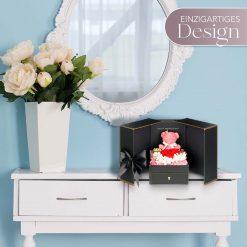 Geschenkbox mit Teddy und roten Infinityrosen steht auf einer Kommode