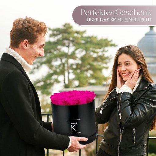 Mann der einer Frau eine schwarze runde Rosenbox mit lila pinken Infinityrosen überreicht