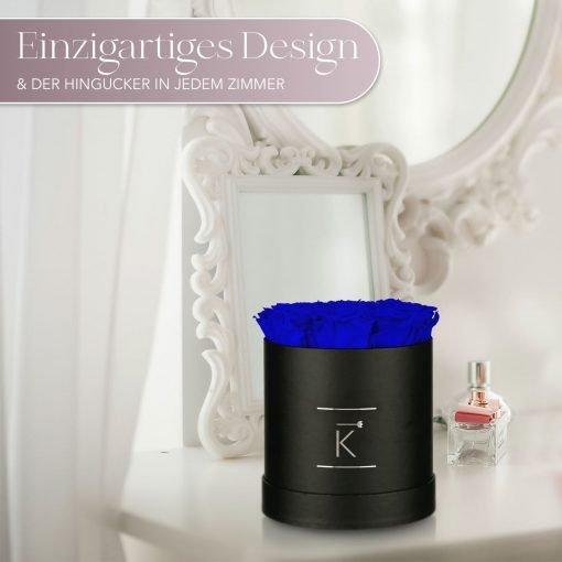Kleine runde Rosenbox in schwarz mit blauen Infinityrosen, die auf dem Schminktisch steht