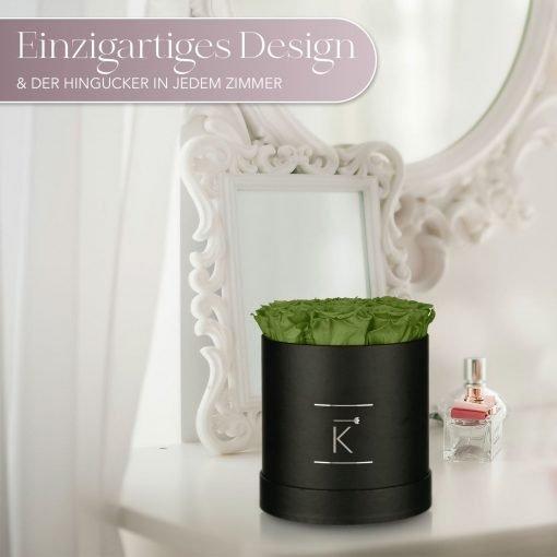 Kleine runde Rosenbox in schwarz mit grünen Infinityrosen, die auf dem Schminktisch steht