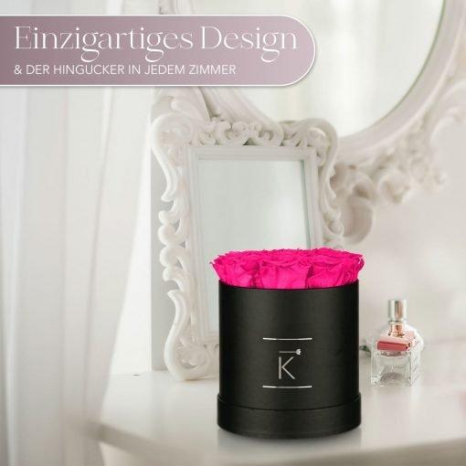 Kleine runde Rosenbox in schwarz mit lila pinken Infinityrosen, die auf dem Schminktisch steht
