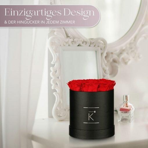 Kleine runde Rosenbox in schwarz mit roten Infinityrosen, die auf dem Schminktisch steht