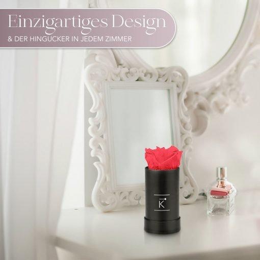 Kleine Rosenbox mit einer pfirsichrosanen Infinityrose, die auf einem Schminktisch steht
