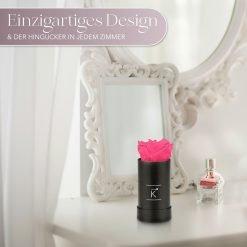 Kleine Rosenbox mit einer pinken Infinityrose, die auf einem Schminktisch steht