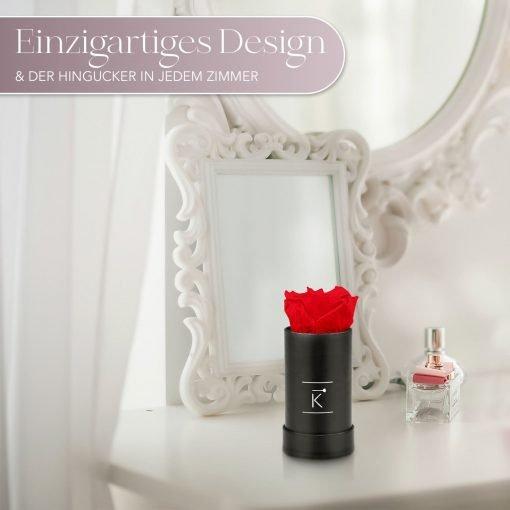 Kleine Rosenbox mit einer roten Infinityrose, die auf einem Schminktisch steht