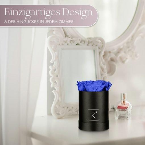 Kleine runde Rosenbox in schwarz mit blauen Infinityrosen die auf dem Schminktisch steht