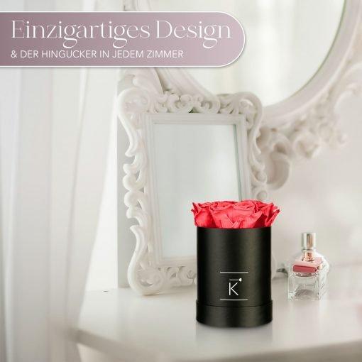 Kleine runde Rosenbox in schwarz mit pfirsichrosanen Infinityrosen, die auf dem Schminktisch steht