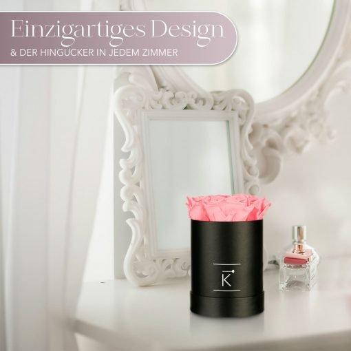 Kleine runde Rosenbox in schwarz mit pinken Infinityrosen, die auf dem Schminktisch steht