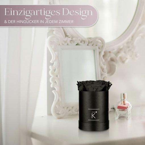 Kleine runde Rosenbox in schwarz mit schwarzen Infinityrosen, die auf dem Schminktisch steht