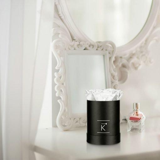 Kleine runde Rosenbox in schwarz mit weißen Infinityrosen, die auf dem Schminktisch steht