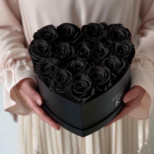 Herzförmige Rosenbox mit schwarzen Infinityrosen wird in den Händen gehalten