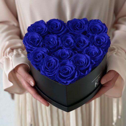 Herzförmige Rosenbox mit blauen Infinityrosen wird in den Händen gehalten