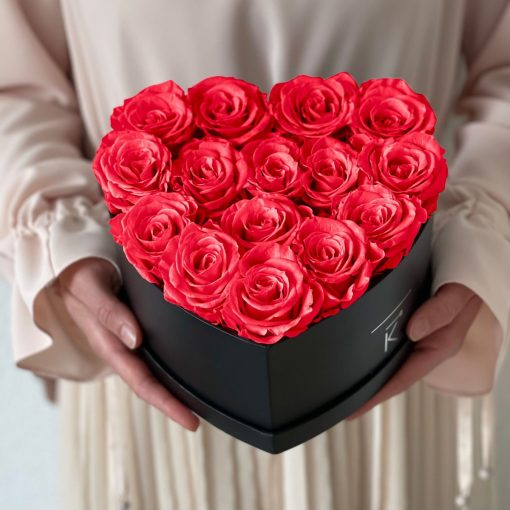 Herzförmige Rosenbox mit orangen pinken Infinityrosen wird in den Händen gehalten