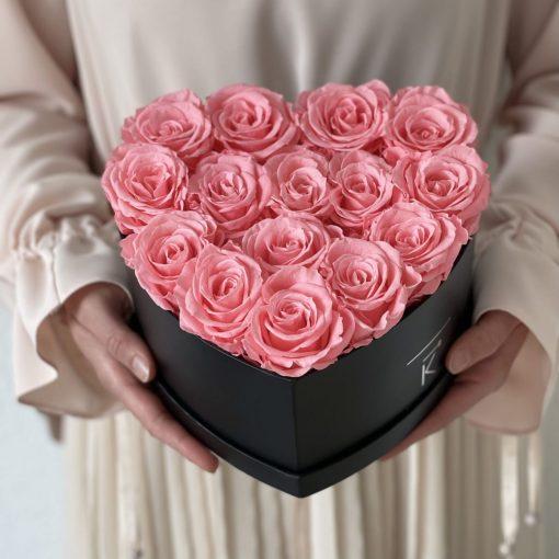 Herzförmige Rosenbox mit pinken Infinityrosen wird in den Händen gehalten
