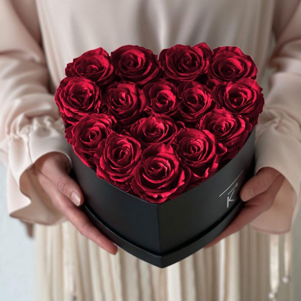 Herzförmige Rosenbox mit roten Infinityrosen wird in den Händen gehalten