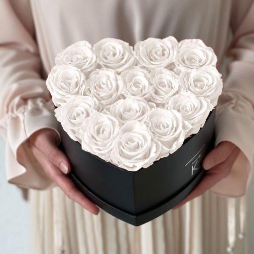 Herzförmige Rosenbox mit weißen Infinityrosen wird in den Händen gehalten