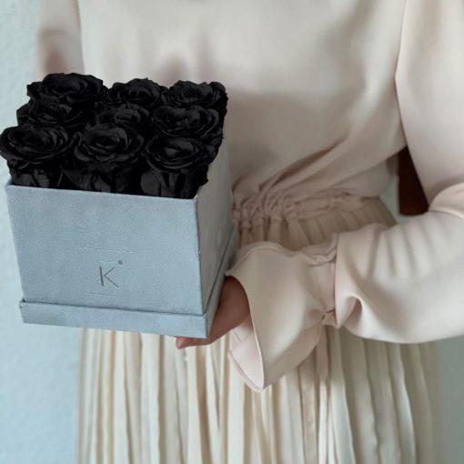 Eckige Rosenbox mit Samtfinish und schwarzen Infinityrosen wird von einer Frau in den Händen gehalten
