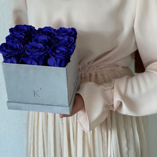 Eckige Rosenbox mit Samtfinish und blauen Infinityrosen wird von einer Frau in den Händen gehalten