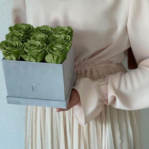Eckige Rosenbox mit Samtfinish und grünen Infinityrosen wird von einer Frau in den Händen gehalten
