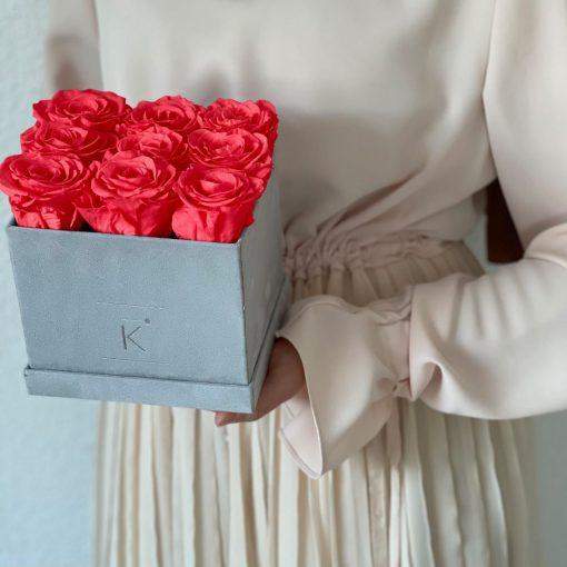 Eckige Rosenbox mit Samtfinish und orangen pinken Infinityrosen wird von einer Frau in den Händen gehalten