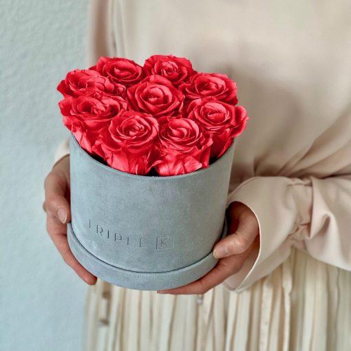 Runde Rosenbox aus hellgrauem Samt mit orangen pinken Infinityrosen wird in den Händen gehalten
