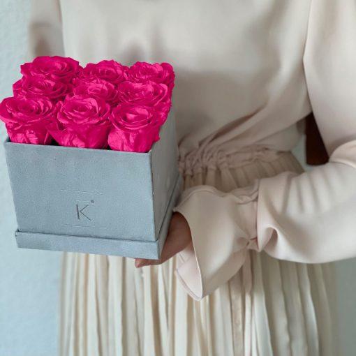 Eckige Rosenbox mit Samtfinish und lila pinken Infinityrosen wird von einer Frau in den Händen gehalten