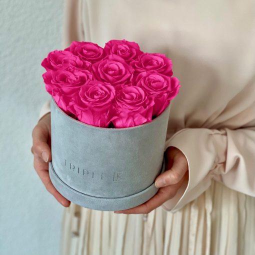 Runde Rosenbox aus hellgrauem Samt mit lila pinken Infinityrosen wird in den Händen gehalten