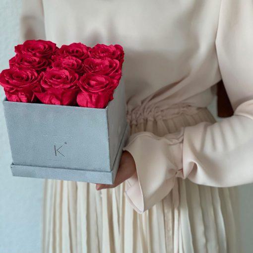Eckige Rosenbox mit Samtfinish und roten Infinityrosen wird von einer Frau in den Händen gehalten