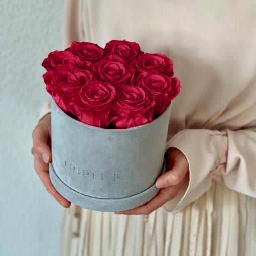 Runde Rosenbox aus hellgrauem Samt mit roten Infinityrosen wird in den Händen gehalten