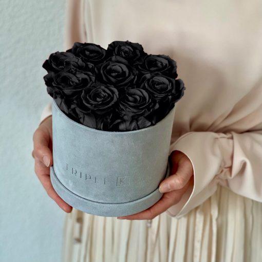 Runde Rosenbox aus hellgrauem Samt mit schwarzen Infinityrosen wird in den Händen gehalten