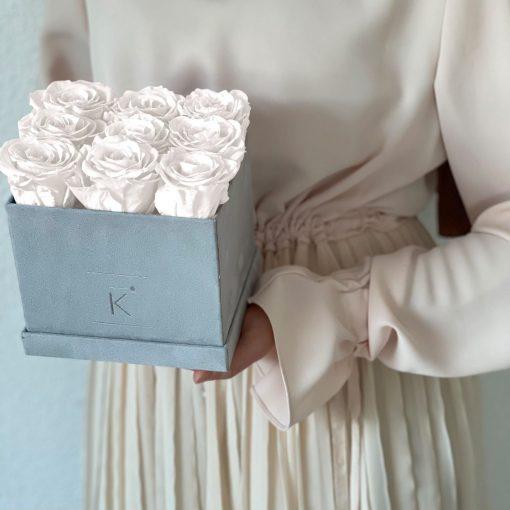 Eckige Rosenbox mit Samtfinish und weißen Infinityrosen wird von einer Frau in den Händen gehalten