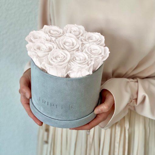 Runde Rosenbox aus hellgrauem Samt mit weißen Infinityrosen wird in den Händen gehalten