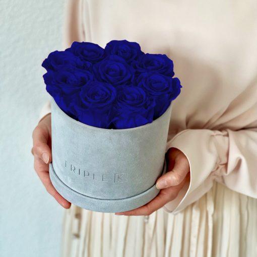 Runde Rosenbox aus hellgrauem Samt mit blauen Infinityrosen wird in den Händen gehalten
