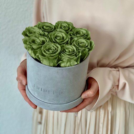 Runde Rosenbox aus hellgrauem Samt mit grünen Infinityrosen wird in den Händen gehalten