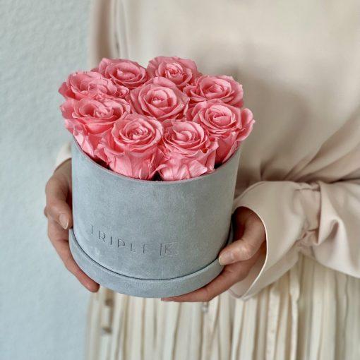 Runde Rosenbox aus hellgrauem Samt mit pinken Infinityrosen wird in den Händen gehalten