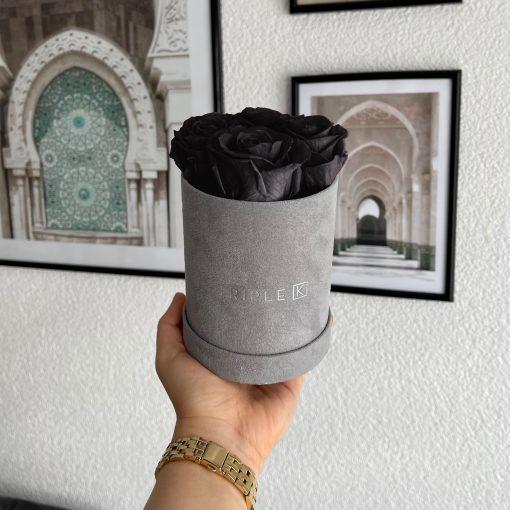 Kleine Rosenbox Samtfinish mit 4 schwarzen Infinityrosen wird von einer Frau in der Hand gehalten