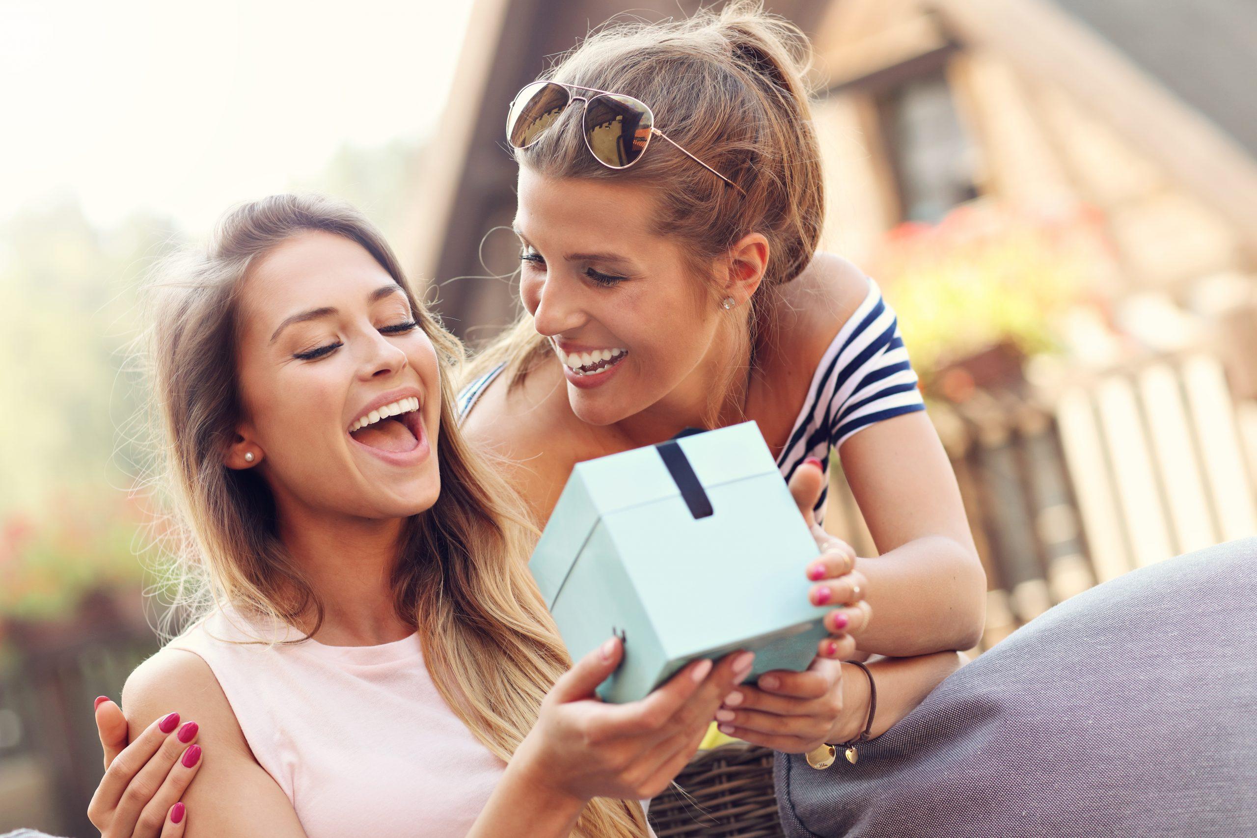 Freundin überreicht Geschenk an Freundin