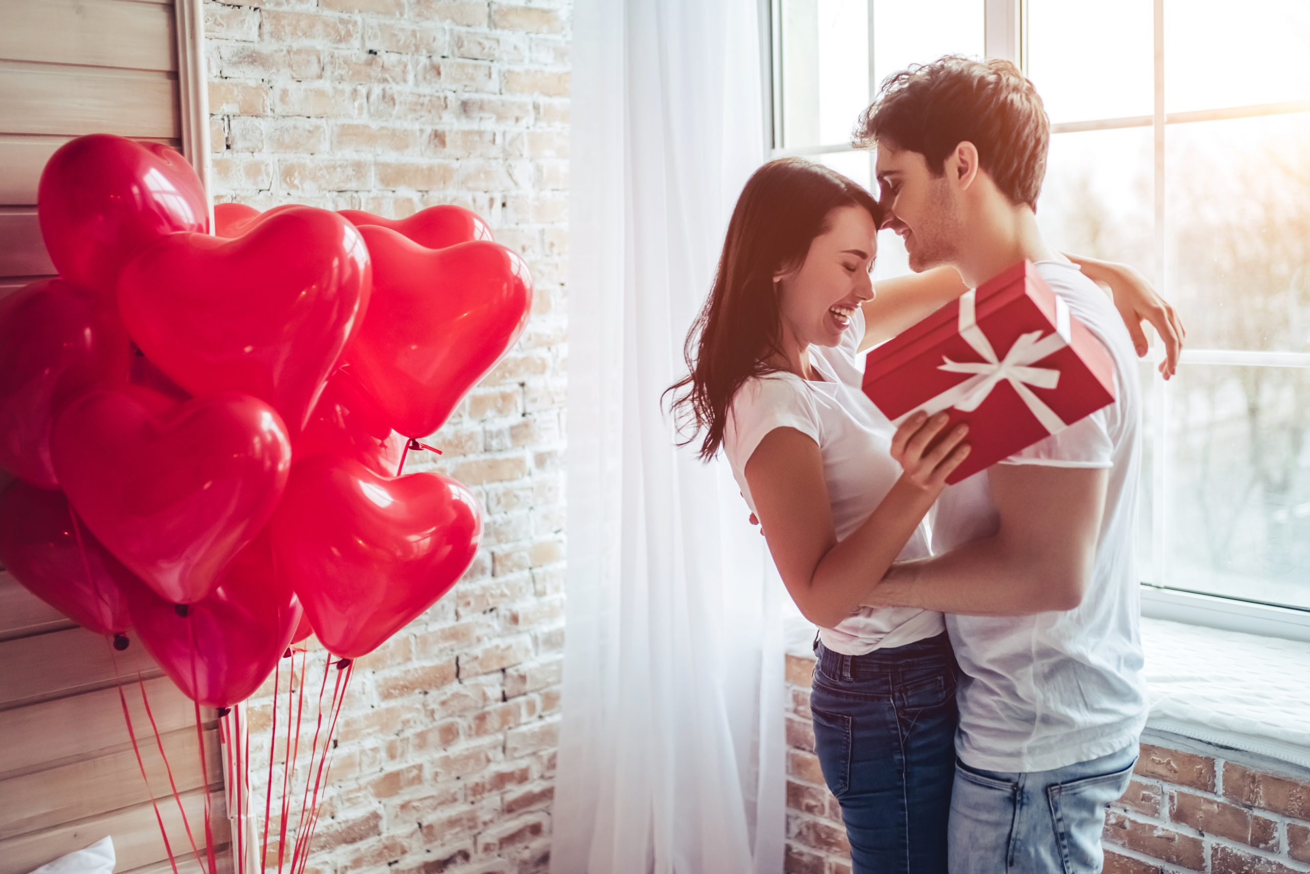 Verliebtes Paar am Valentinstag, Frau übergibt Geschenk an Mann, im Hintergrund rote Herzchenballons