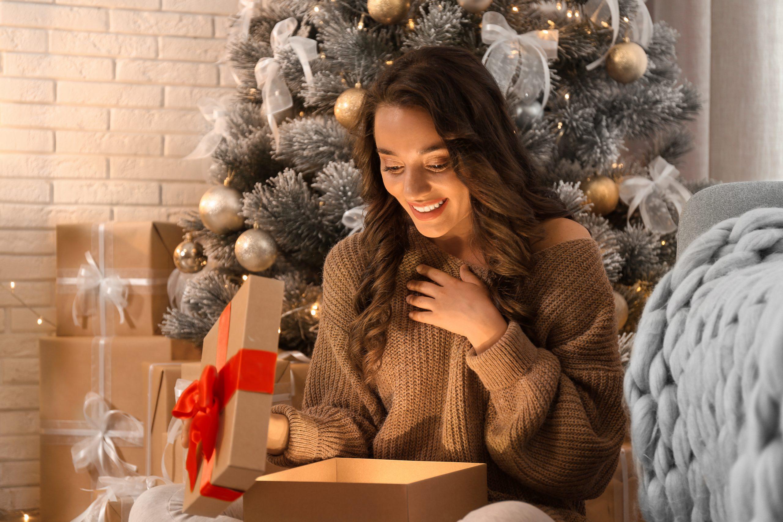 Frau sitzt vor Weihnachtsbaum und öffnet eine Geschenkverpackung