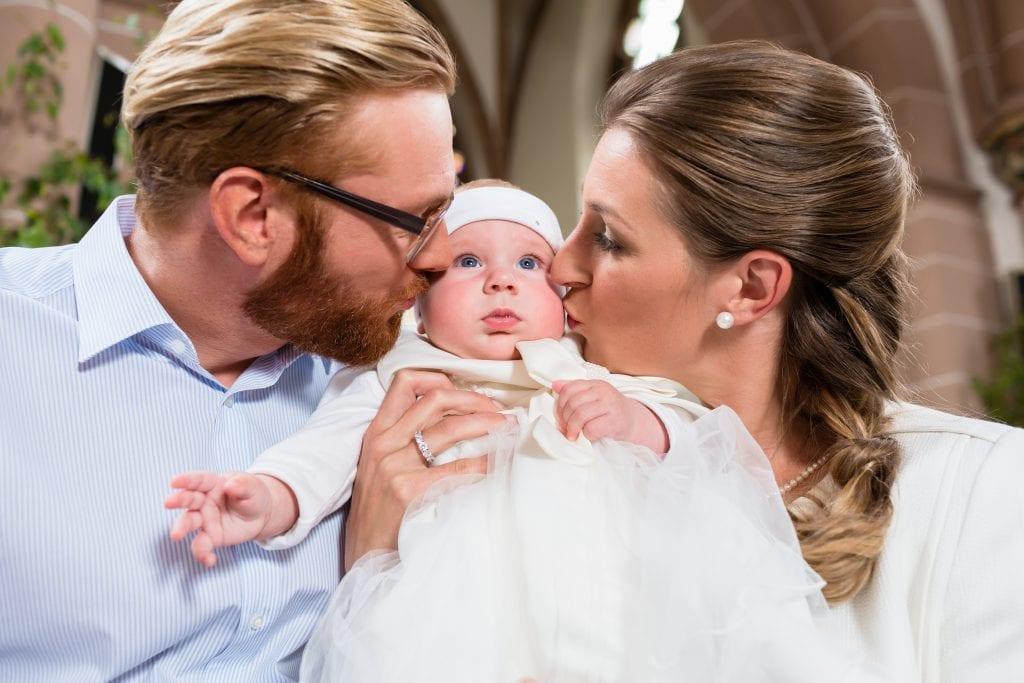 Eltern mit Baby auf dem Arm bei der Taufe