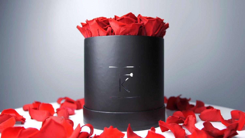 Rosenbox schwarz rund mit roten Rosen, im Hintergrund rote Rosenblätter