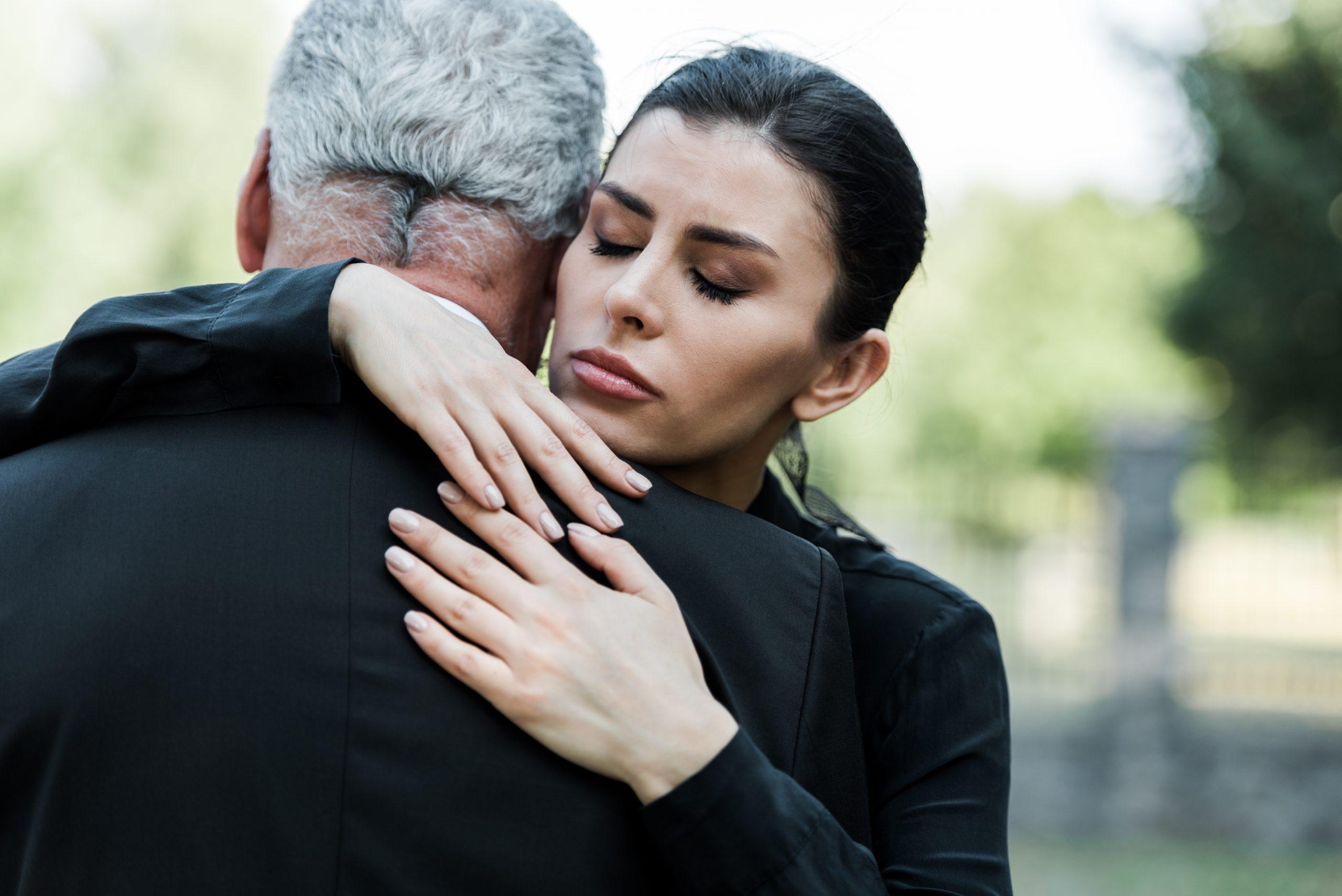 Schwarz gekleideter Mann umarmt eine Frau bei einer Beerdigung