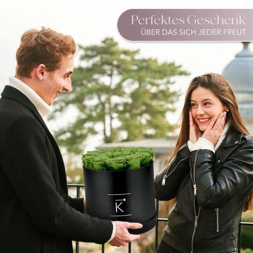 Mann der einer Frau eine schwarze runde Rosenbox mit grünen Infinityrosen überreicht