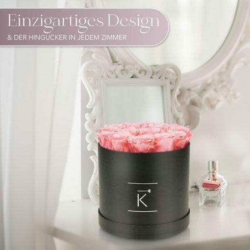 Große runde Rosenbox mit rosanen Infinityrosen, die auf einem Schminktisch steht