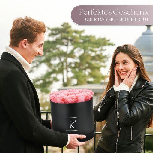Mann der einer Frau eine schwarze runde Rosenbox mit rosanen Infinityrosen überreicht