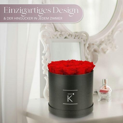 Große runde Rosenbox mit roten Infinityrosen, die auf einem Schminktisch steht