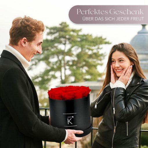 Mann der einer Frau eine schwarze runde Rosenbox mit roten Infinityrosen überreicht