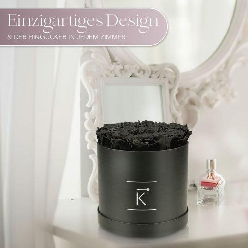 Große runde Rosenbox mit schwarzen Infinityrosen, die auf einem Schminktisch steht