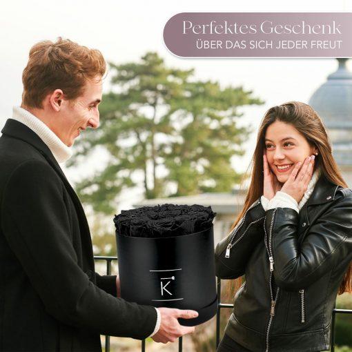 Mann der einer Frau eine schwarze runde Rosenbox mit schwarzen Infinityrosen überreicht
